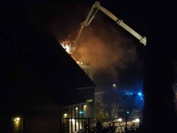 Veel rook komt er uit de woning, de brandweer ter plaatse