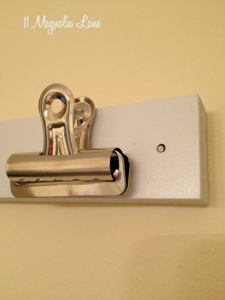 Drill a hole and use a wire brad nail to mount the board on the wall.