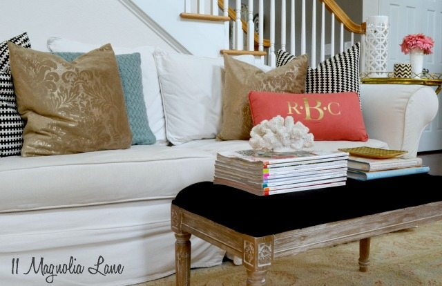 Living room in black, white, coral, and gold