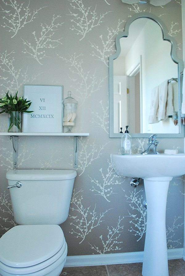 Easy updates to a builder grade small powder room. Add temporary wallpaper, spray paint a mirror and build in a shelf. Huge impact for small $..