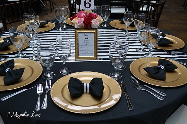 Bowtie folded napkins on black, white, and gold table setting