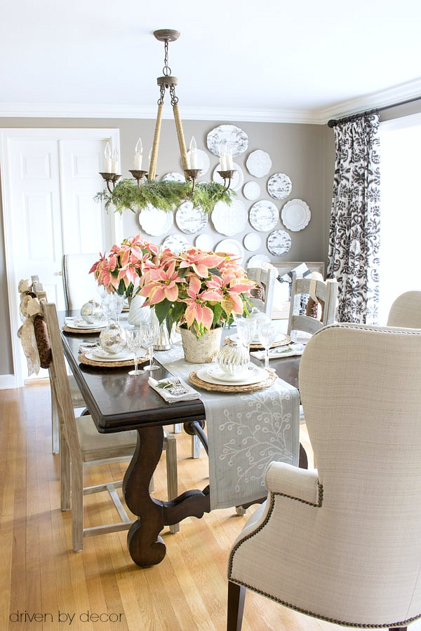 dining-room-decorated-for-christmas-with-pink-poinsettias-and-gold-and-silver-ornaments-and-trees