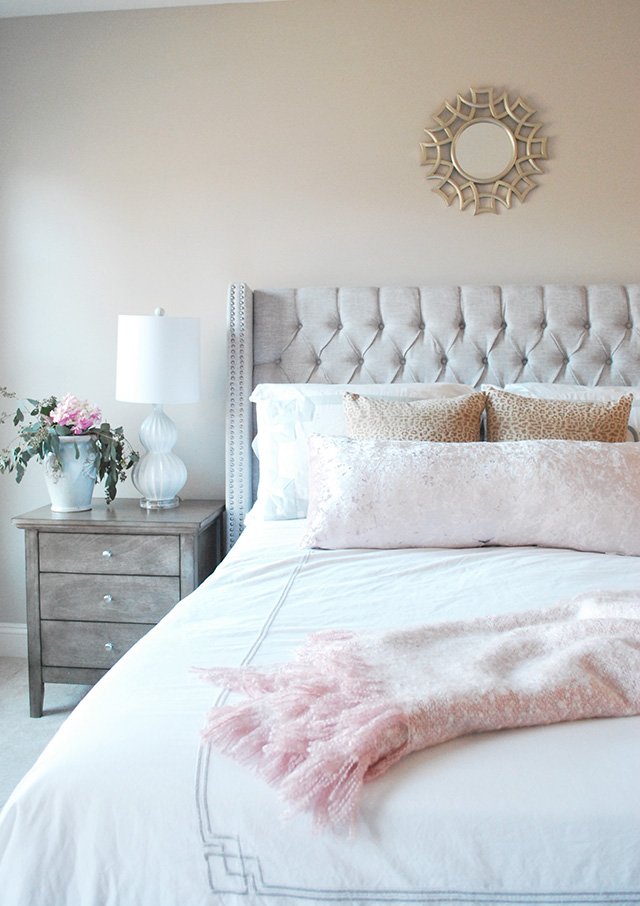 A soothing master bedroom with tones of blush, gray and gold.
