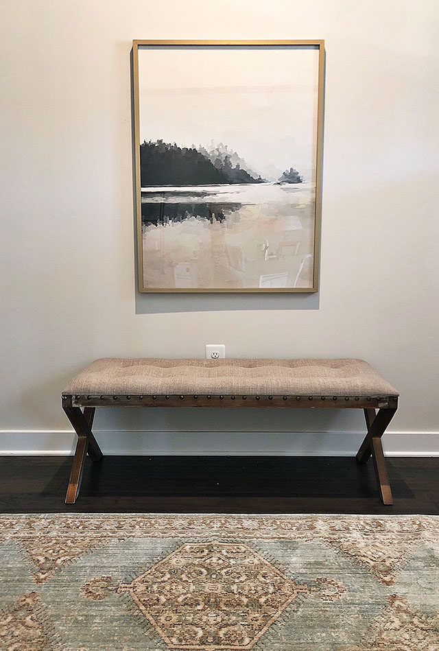 An affordable bench and art decorate a long hallway