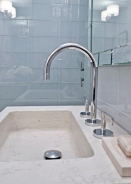 Limestone sink with gooseneck bath faucet set against glass tiles the color of a cloudy day