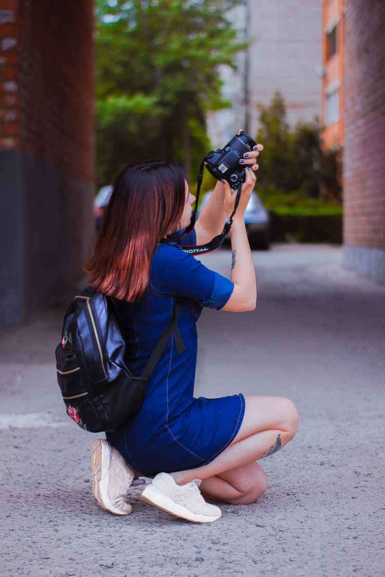photography of a woman kneeling while taking a picture