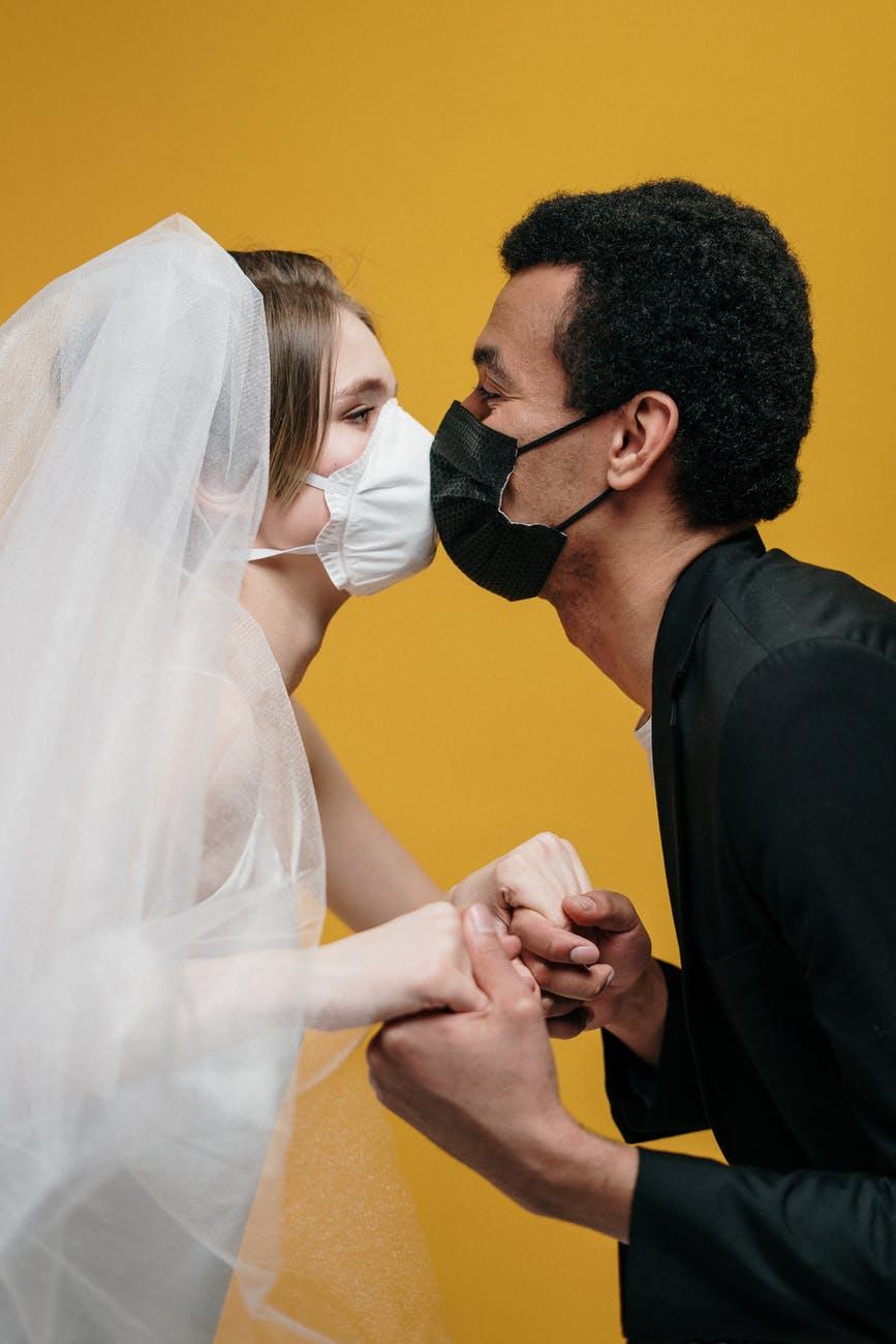 man in black suit jacket holding woman in white wedding dress