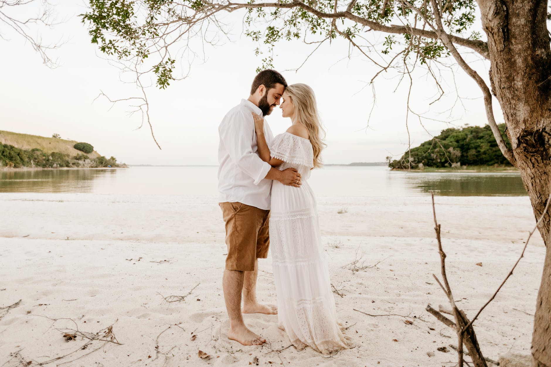 elegant couple embracing on sandy sea shore during summer trip