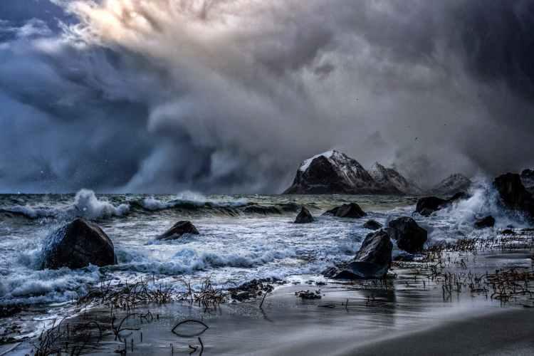 stormy sea near rocks under dramatic sky in hurricane weather