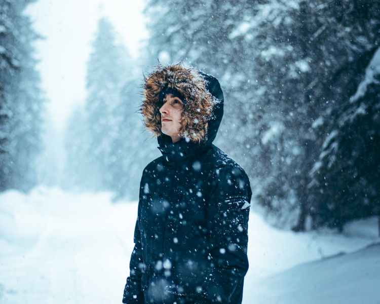 woman in black jacket standing on snow covered ground