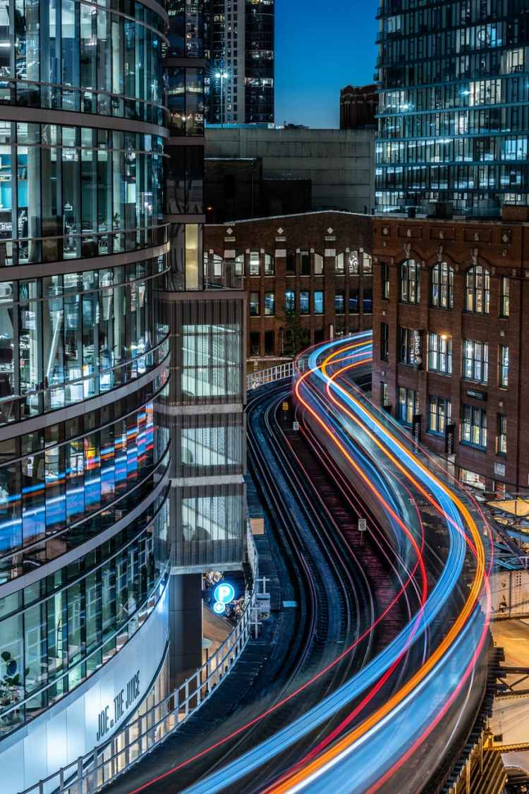time lapse photography of railway and building during nighttime