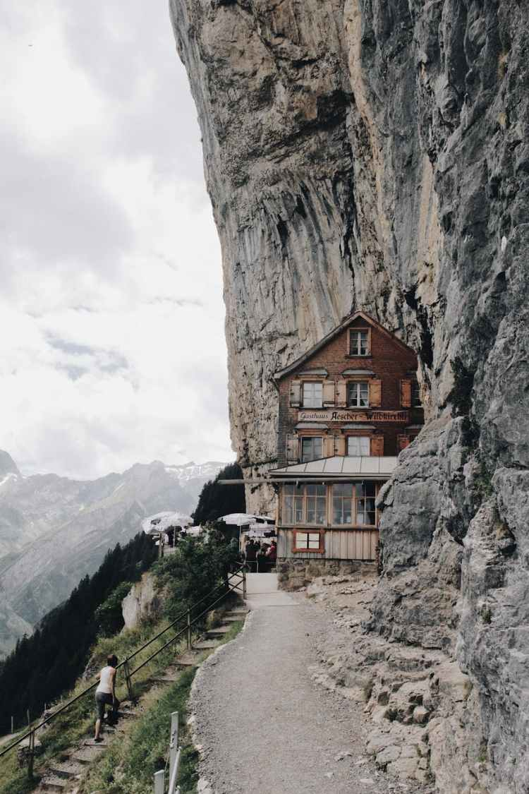 brown wooden house on edge of cliff