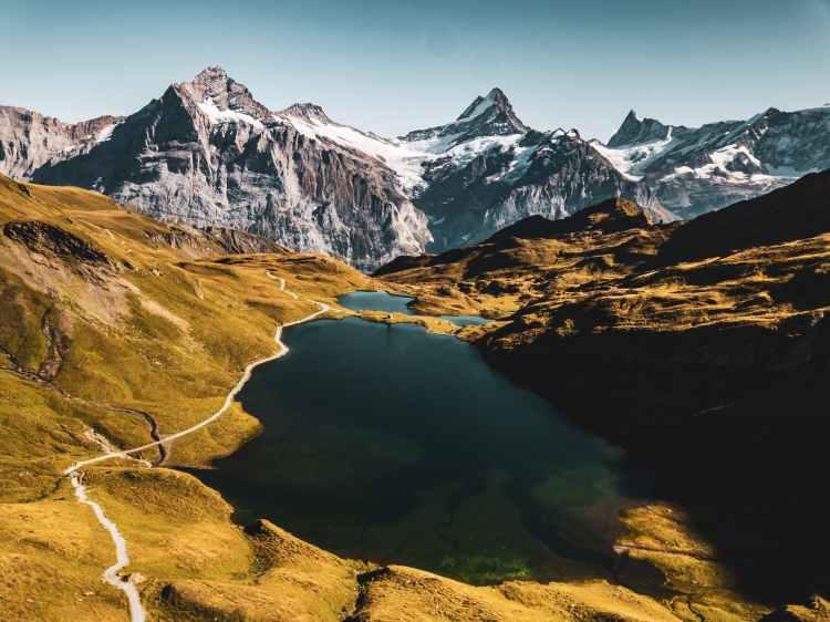 scenic photo of lake across mountain range