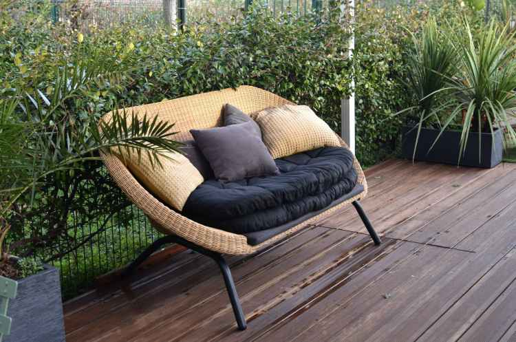 cozy rattan sofa with cushions in tropical garden