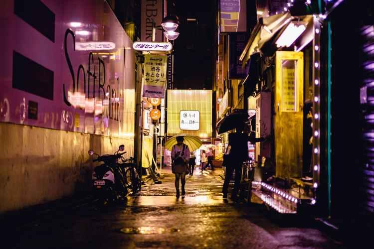 people walking near road beside buildings during night time