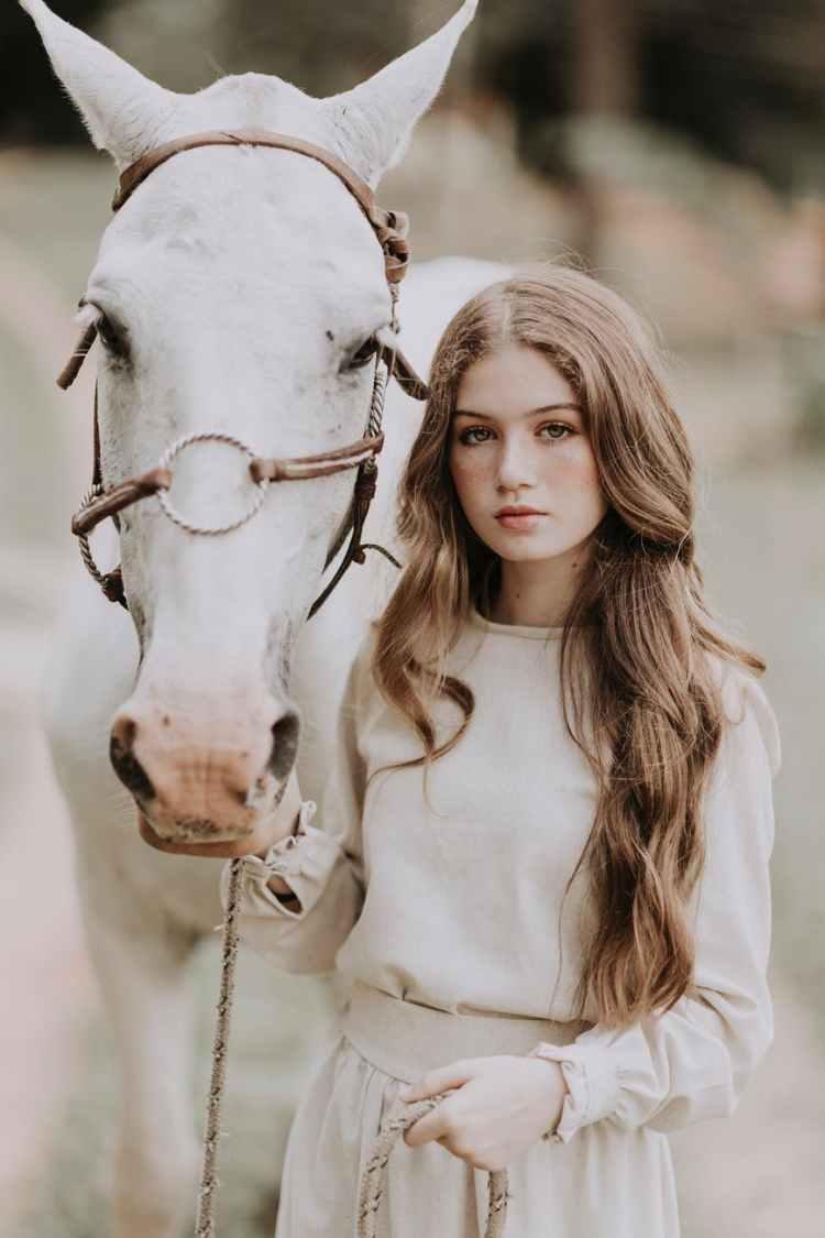 woman with stallion on pasture
