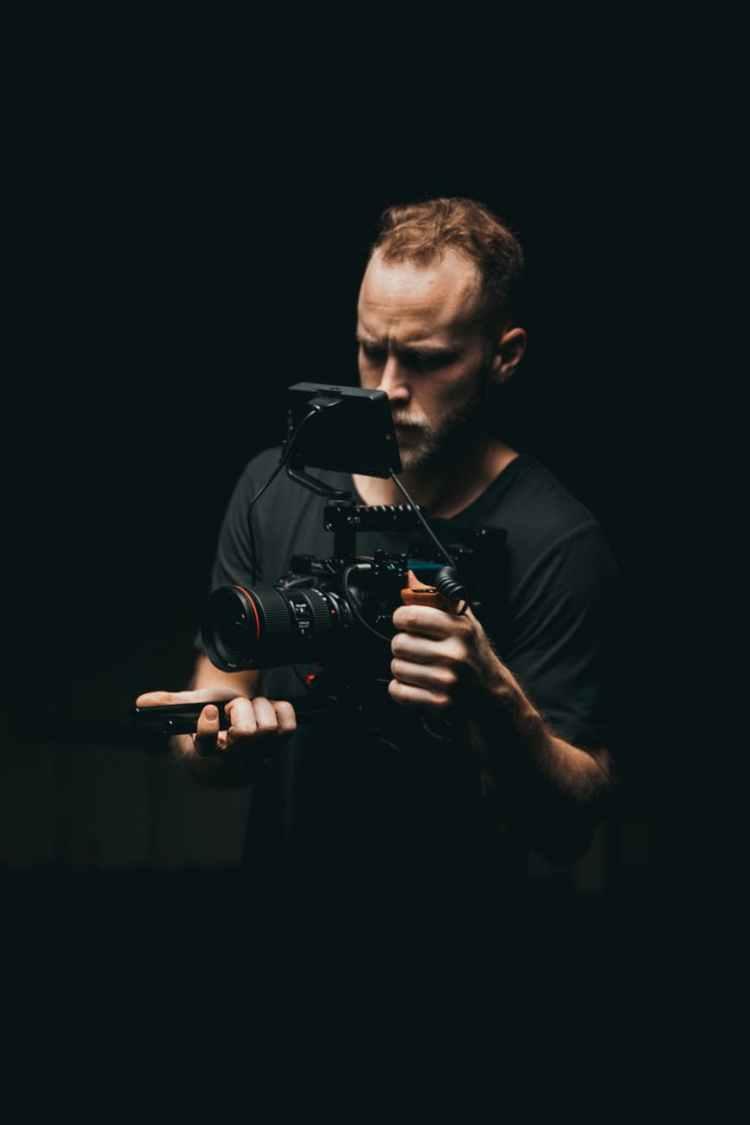 shallow focus photo of man wearing black dslr camera