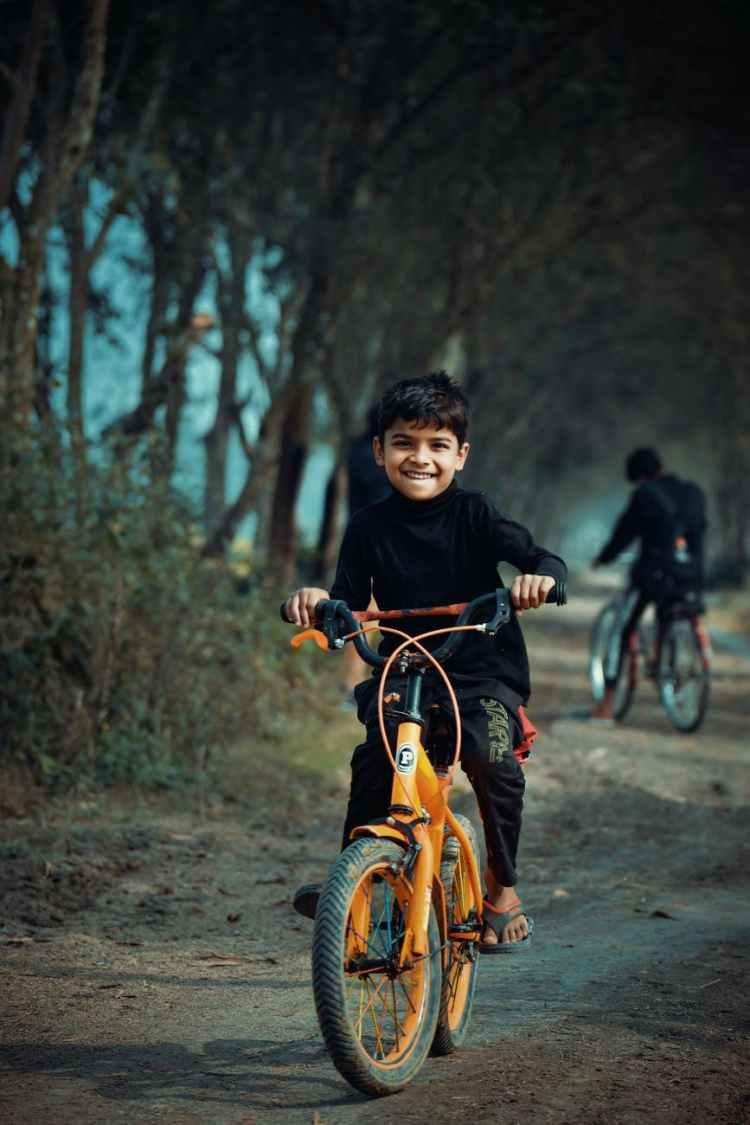 boy in black long sleeved shirt riding orange bicycle