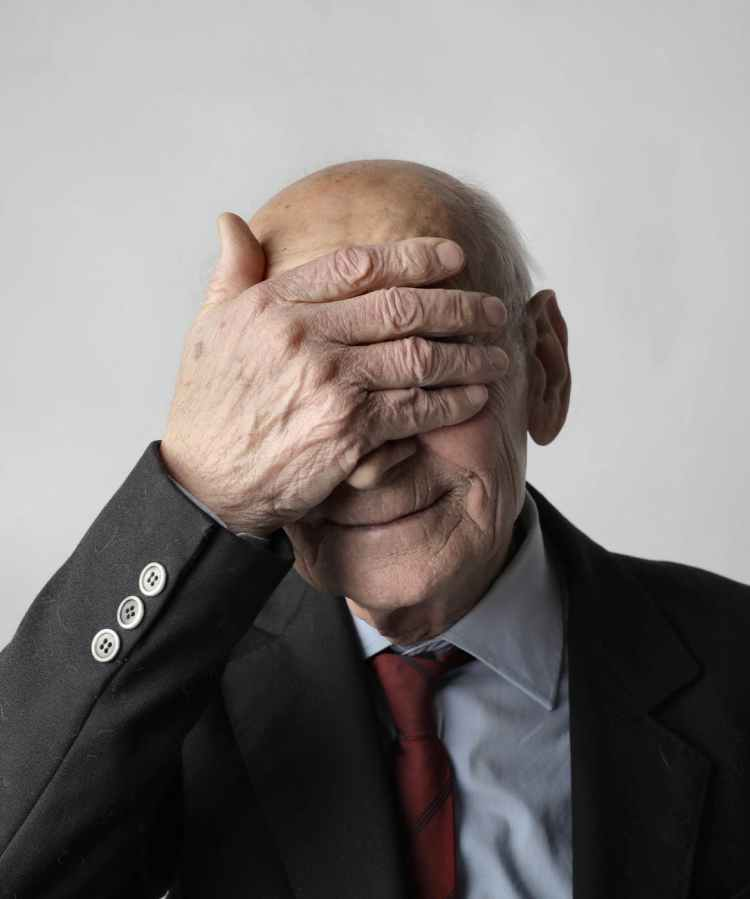 elderly man in black suit jacket covering his eyes with his hand