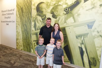The new Kay Jewelers Pavilion features large photographs throughout, including this one of NICU grads Gavin and Matthew Jenkins, who are standing in front of it with their parents Kelly and Mike.