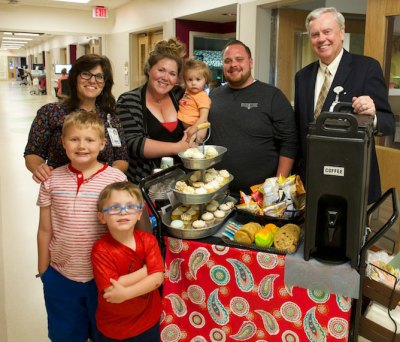 PAC coordinator Judy Doyle (left) and Akron Children's CEO Bill Considine (right) offer a family refreshments from the coffee cart.