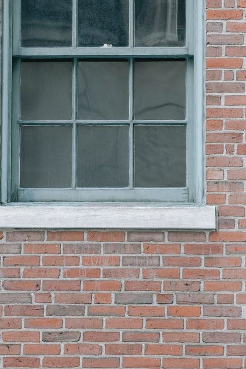 wooden window in brick wall of building