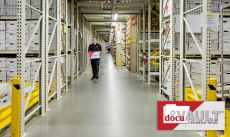Man walking through isles of documents stored on DocuVaults premises