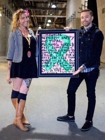 [Emily T. Nielsen & Tim Mcilrath (of Rise Against) with the original art piece that started Rock Vs. Cancer, and lead into Punk Rock & Paintbrushes]