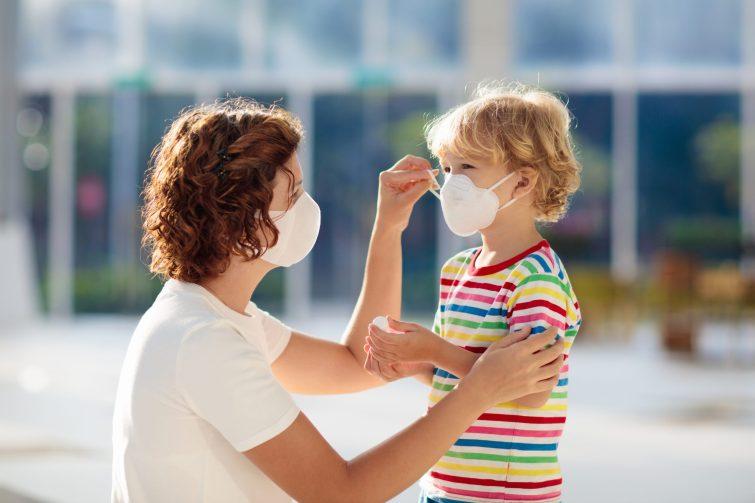 mom putting mask on kid