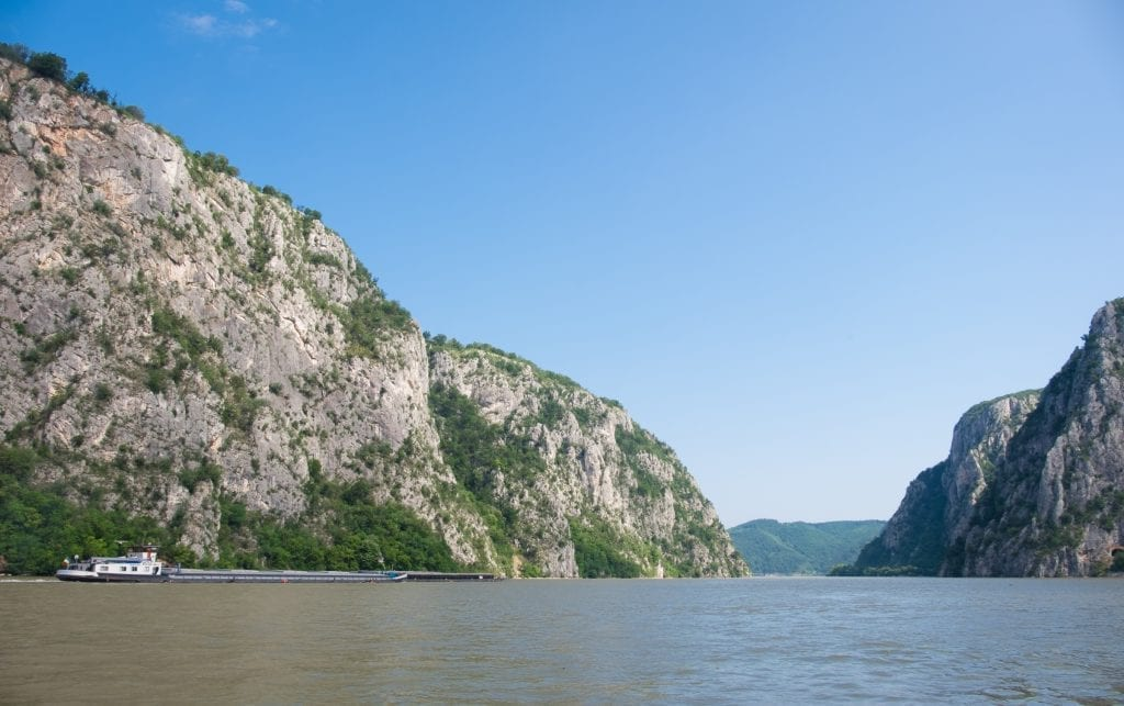 Tall limestone cliffs on the Danube and a boat with a long, flat platform for shipping goods.