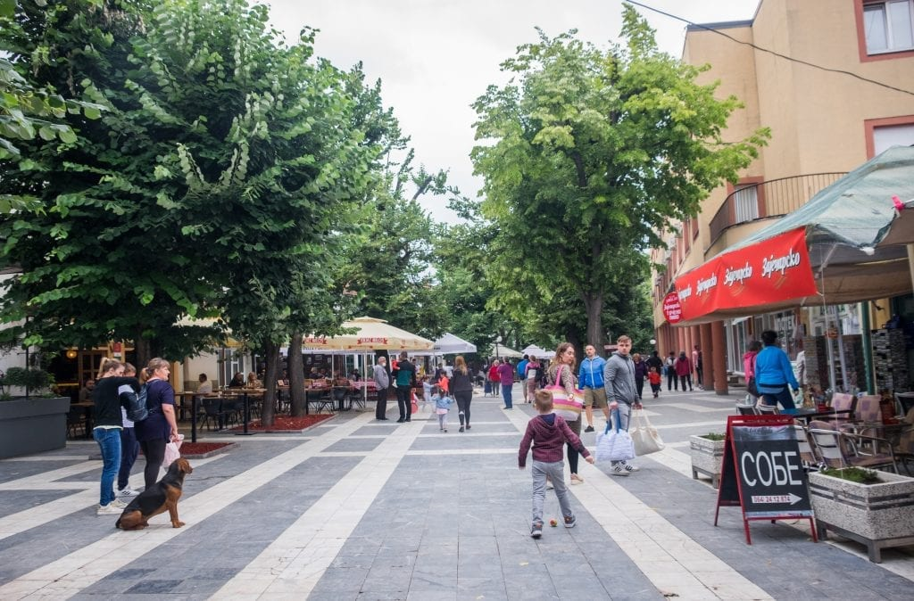 A pedestrian-only street in Sokobanja lined with shops, people walking down the street.