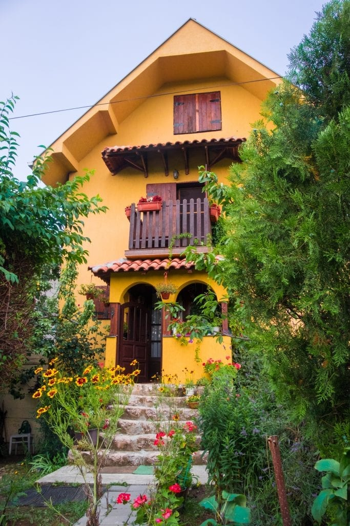 A yellow country house set in a garden full of flowers.