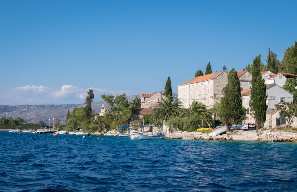 Vrnik Island, with buildings and cypress trees, as seen from the ocean.