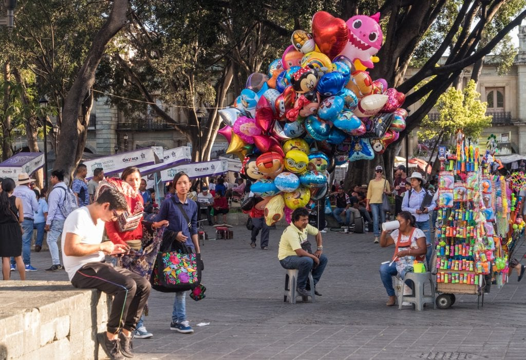 Crowds on a street in Oaxaca, including a balloon seller, a toy seller, and people walking around with friends.