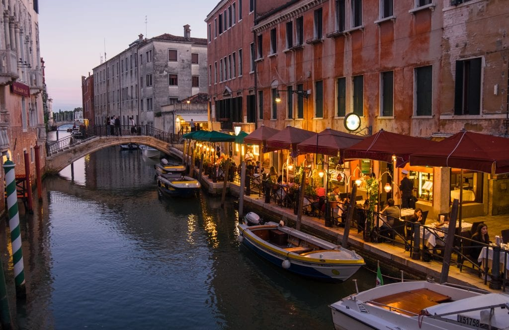 People sitting at a restaurant lit by golden street lamps on the edge of a canal, small wooden boats in the canal.