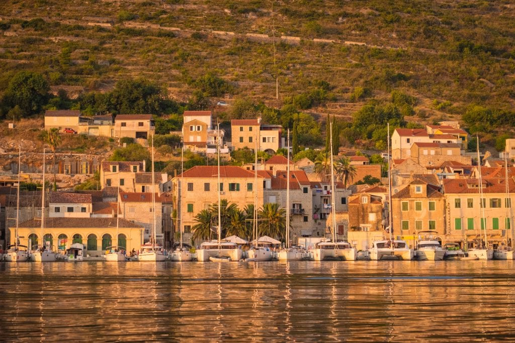 Sunrise in Vis: a view across the water, white sailboats lined up on the shore, sun-drenched brick buildings and hills in the background.