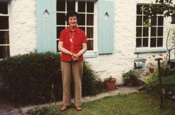 Doreen Tovey in front of cottage