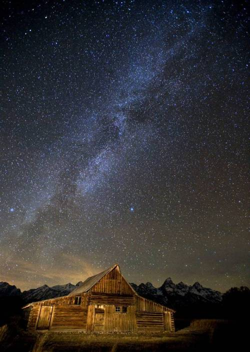 The Milky Way spreads across the night sky over Mormon Row, a historic settlement in Grand Teton National Park near Jackson, Wyo. The light in the distance is the city of Driggs, Idaho, on the west side of the Teton Mountain Range.source