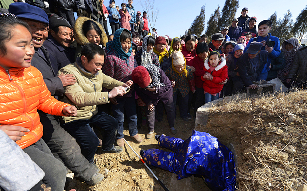 Sixty-six-year-old Zheng Deyang climbs into his tomb at a funeral for himself in a village in Rizhao in east China's Shandong province Saturday Feb. 6, 2016. Zhang, who had no children, held a funeral for himself to see whether his relatives and villagers will pay tribute to his death in the future. Zhang is only 1.4-meter tall and did not marry and is not sure whether others remember his good deeds to the village. Photo via Newscom