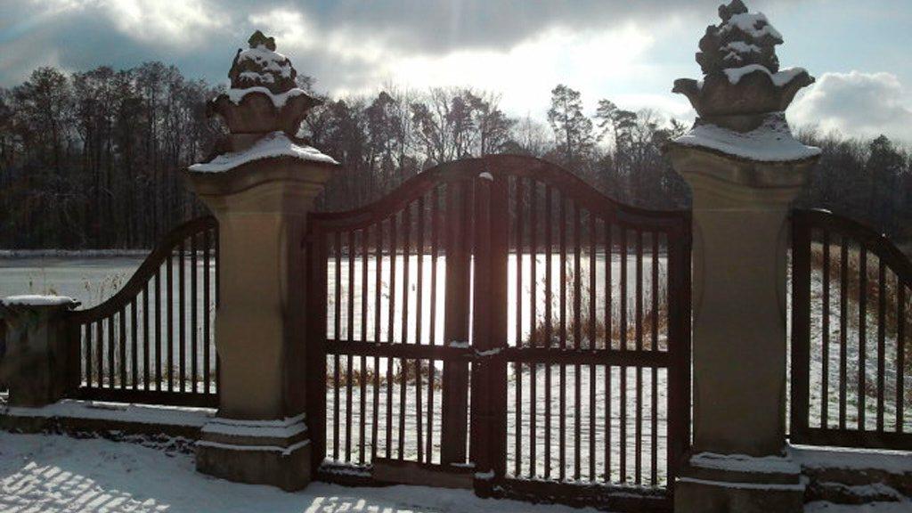 Tor in verschneiter Landschaft, durch die Gitterstäbe des Tores kann auf den verschneiten See sehen.
