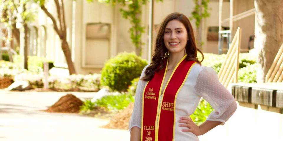 Vanessa Pangbourne, USC Viterbi graduate and SHPE-USC president, photographed wearing a white blouse and graduation sash showcasing her leadership, standing in a courtyard at USC, smiling into the camera.