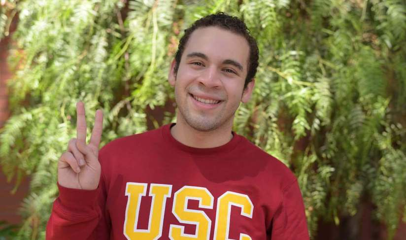 """Carlos Acosta is smiling, wearing a USC sweater, and is posing with the """"Fight On!"""" hand sign."""