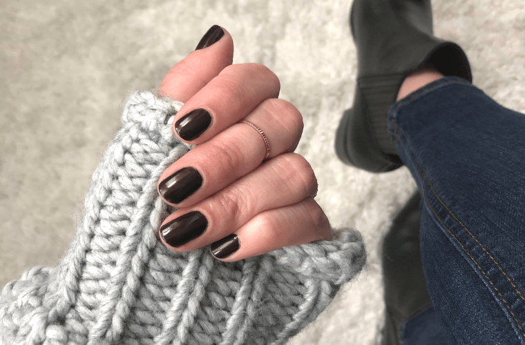 photo of fingers holding grey sweater and wearing dark nail polish