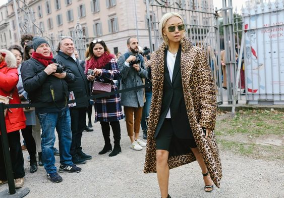 Woman wearing sunglasses, and a leopard print jacket.