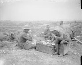 Officers dining. One is wearing a private's uniform. Near Bernafay Wood, July 1916 © IWM (Q 4053)