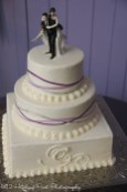 Square cake on bottom with couple's monogram and purple, lavender, and silver ribbons