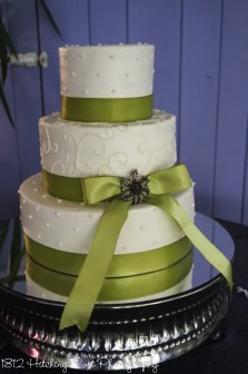 Green ribbon and brooch on wedding cake