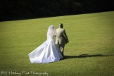 Bride walked across lawn by father