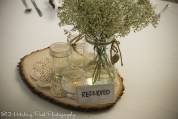 Centerpieces of wood slab with doilies, mason jars, and candles