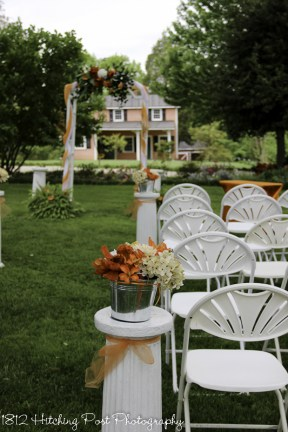 Galvanized buckets with orange, rust, and cream flowers on columns tied with orange ribbon